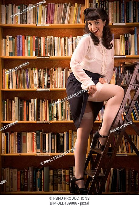 Woman in retro clothing on library ladder