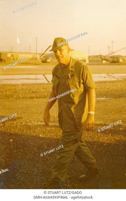 Soldier walking outdoors through open area of camp, Team Three, Vietnam, 1964