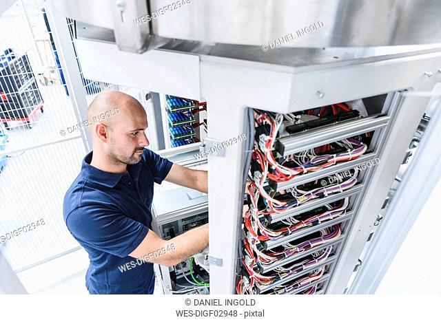 Man using voltmeter in modern factory