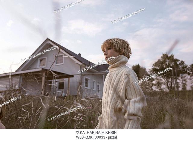 Boy standing in field beside rural house