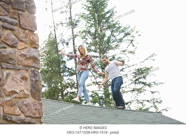Young couple walking on cabin rooftop