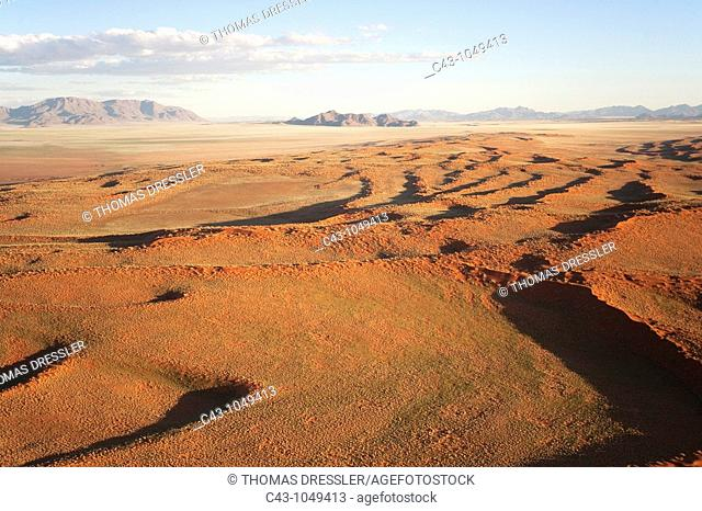 Namibia - Aerial view of grass-grown sand dunes and isolated mountain ridges at the edge of the Namib Desert  In March during the rainy season with a delicate...