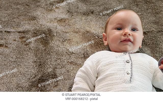 Happy baby lying on a fur rug