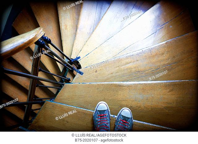 Close-up of feet with sneakers going down old stairs in a building in Paris, France