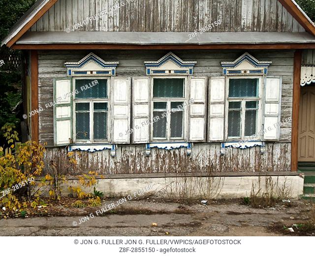 A traditional Russian house, made of wood or timbers and with nalichniki, fancy decorative wood trim, around the windows