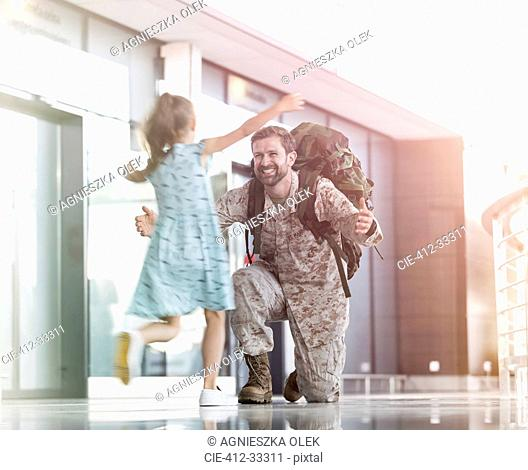 Daughter running and greeting soldier father in airport concourse
