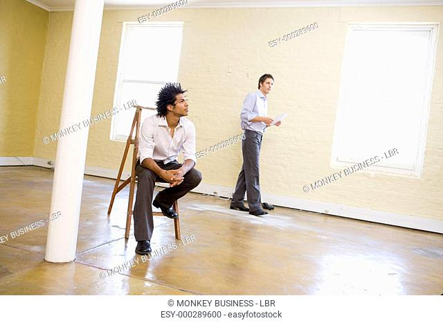 Man sitting on ladder in empty space with another man holding paper