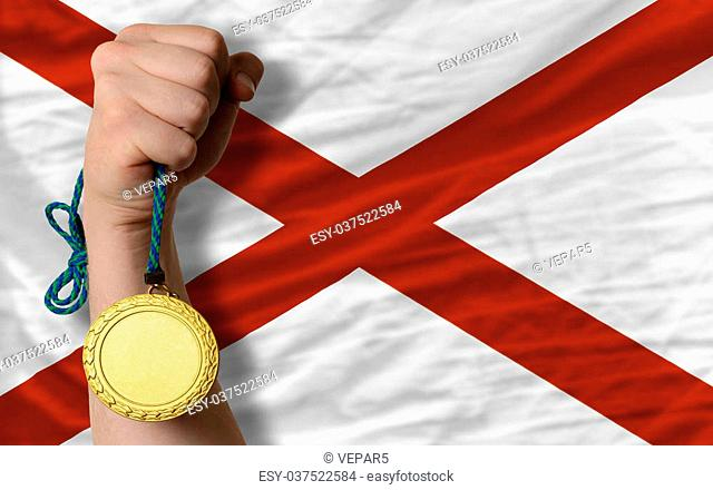 Winner holding gold medal for sport and flag of us state of alabama