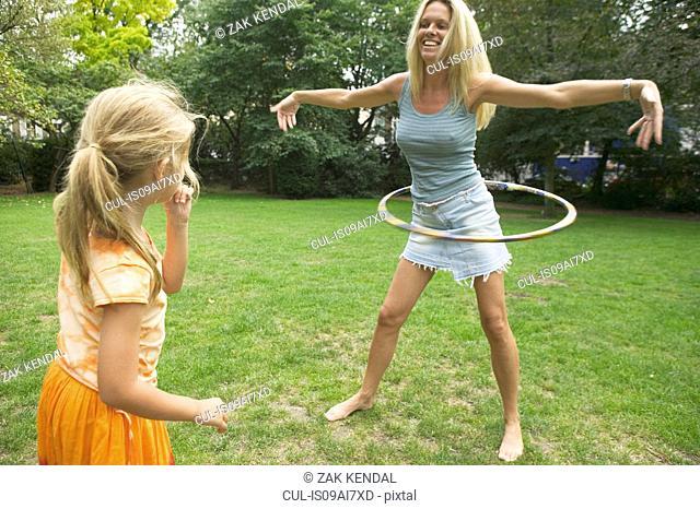 Girl watching mother hula hooping