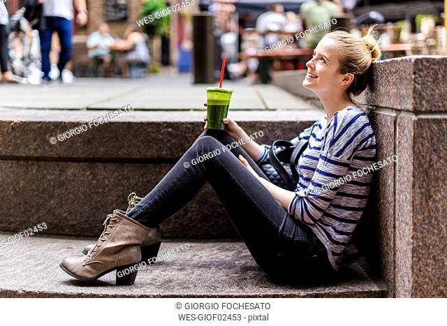 USA, New York City, smiling woman having a break drinking a smoothie in Manhattan