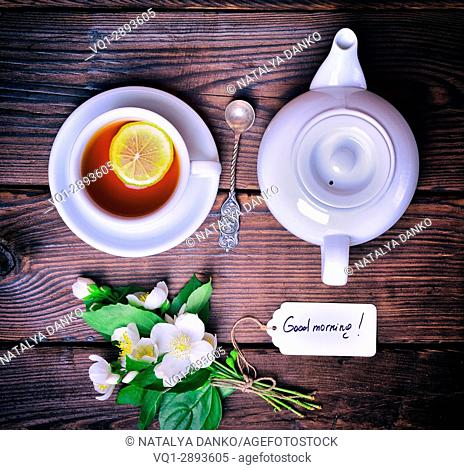 Black tea with lemon and white tea pot, next to a bouquet of flowering jasmine with a paper tag, top view