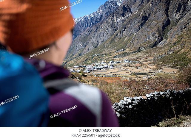 A woman trekking in the Langtang valley rests near a chorten, Langtang Region, Himalayas, Nepal, Asia
