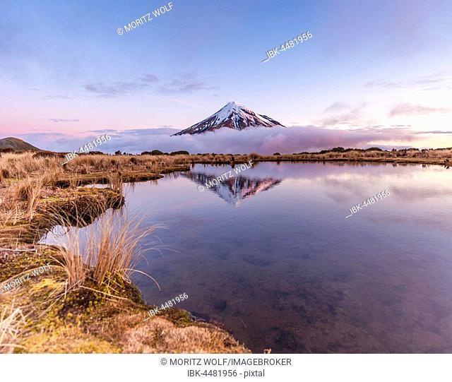 Reflection in Pouakai Tarn lake, clouds around stratovolcano Mount Taranaki or Mount Egmont at sunset, Egmont National Park, Taranaki, New Zealand