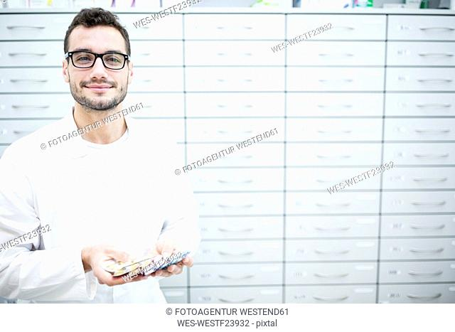 Portrait of smiling pharmacist holding tablet packages at cabinet in pharmacy