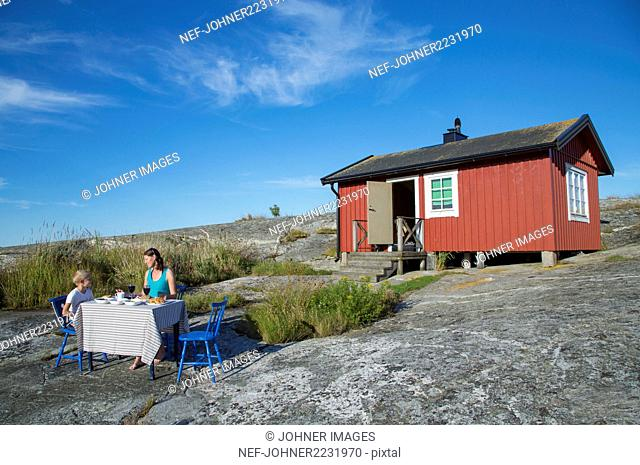 Mother and son having meal in front of weekend cottage
