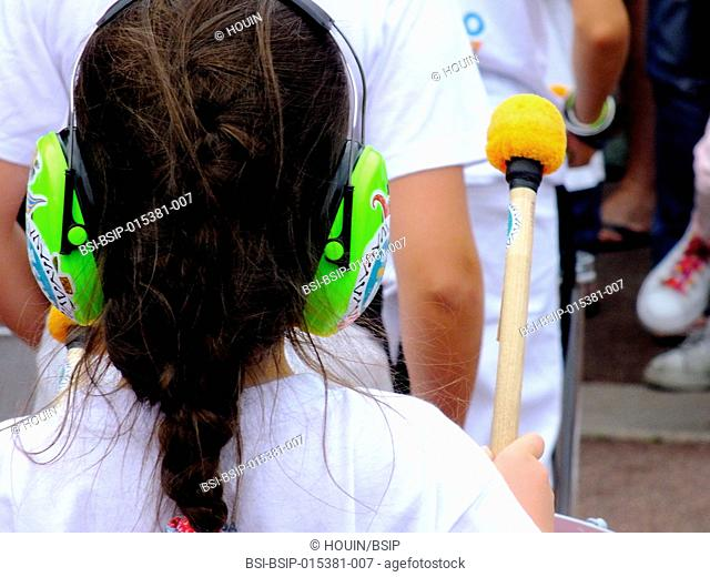A child playing music wearing noise-canceling headphones
