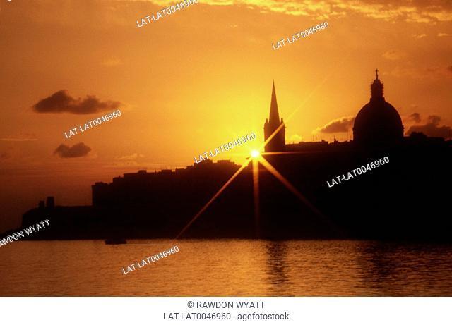 Sun rising over silhouette of buildings. Sea. Orange sky