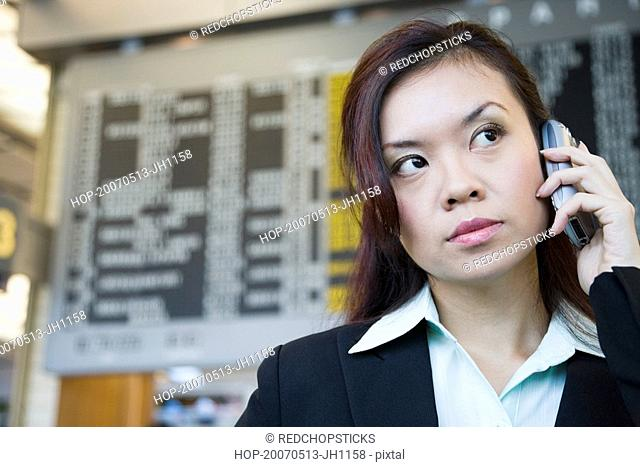 Close-up of a businesswoman at an airport and talking on a mobile phone