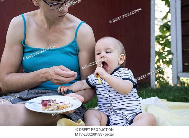 Baby boy eating cake from the plate of his mother in lawn, Munich, Bavaria, Germany