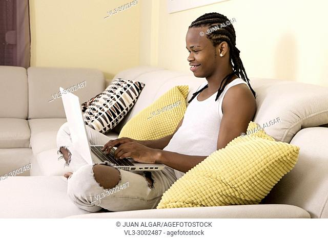 Side view of cheerful young black man typing on laptop while sitting on couch