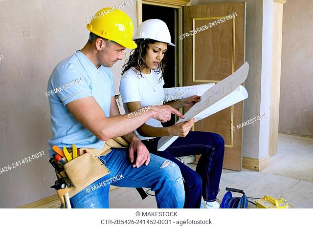Male builder with woman site manager reading plans