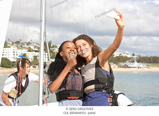 Two young female friends taking self portrait with sailboat
