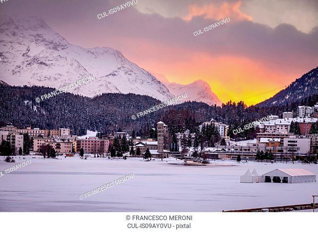 Village beneath mountain on snow covered landscape at sunset, Sankt Moritz, Switzerland