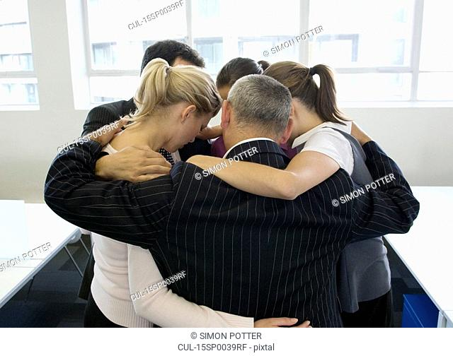 A portrait of a business team huddling