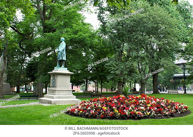 Canada Saint John New Brunswick Kings Square with flowers and Sir Samuel Leonard Tilley statue and relaxing locals in quiet peaceful park