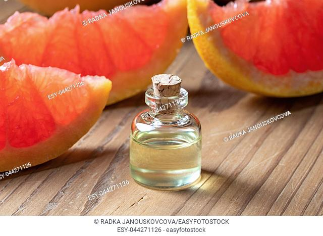 A bottle of citrus essential oil with fresh grapefruit
