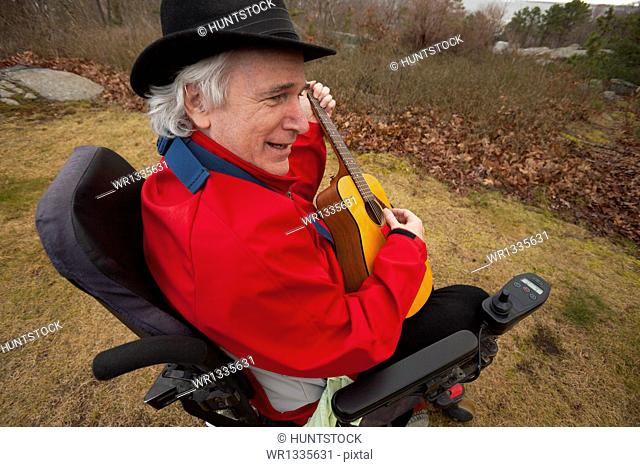 Man with Multiple Sclerosis in a motorized wheelchair enjoying his back yard with his guitar