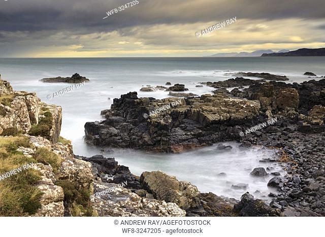 A rocky cove at Dun Ara on the Isle of Mull with the Small Isles in the distance. A long shutter speed was utilized to blur the movement in the water and clouds