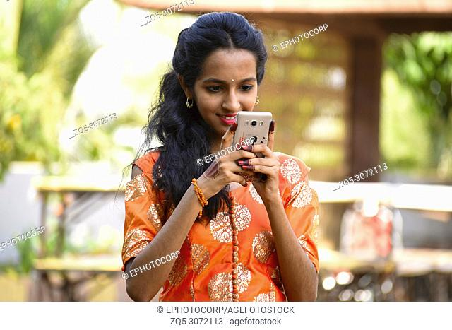 Young girl looking at her mobile, Pune