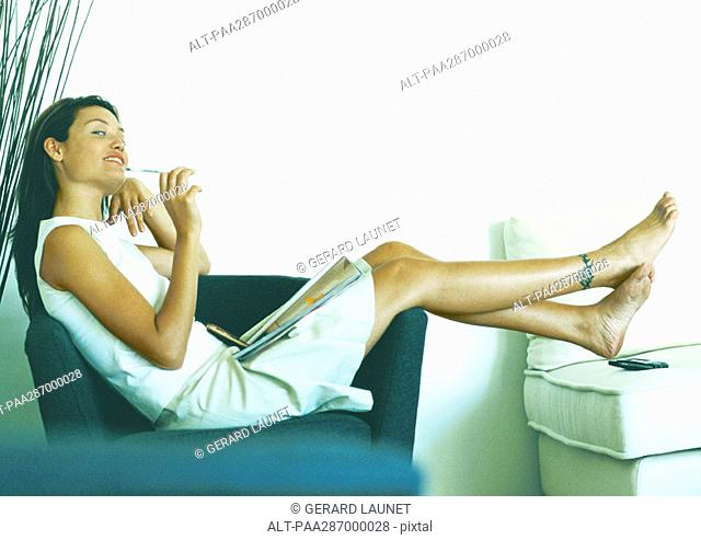 Woman sitting sideways on armchair, full length