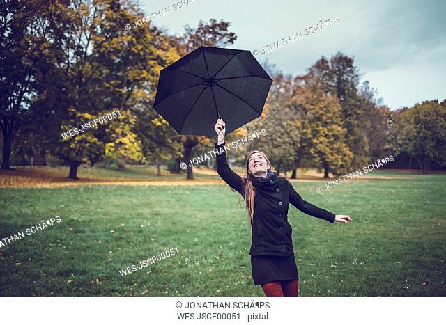 Young woman dancing with umbrella in autumnal park