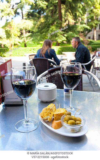 Spanish appetizer: green olives and tapa of Spanish omelet with two glasses of red wine in a terrace. Madrid, Spain