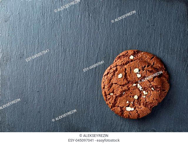 Freshly baked chocolate chips cookies decorated with oatmeal chips isolated on black background, macro, close-up
