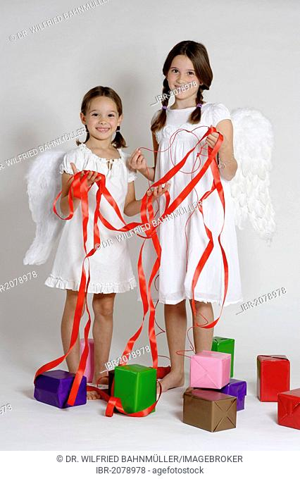 Two girls dressed up as Christmas angels with gifts, Christmas