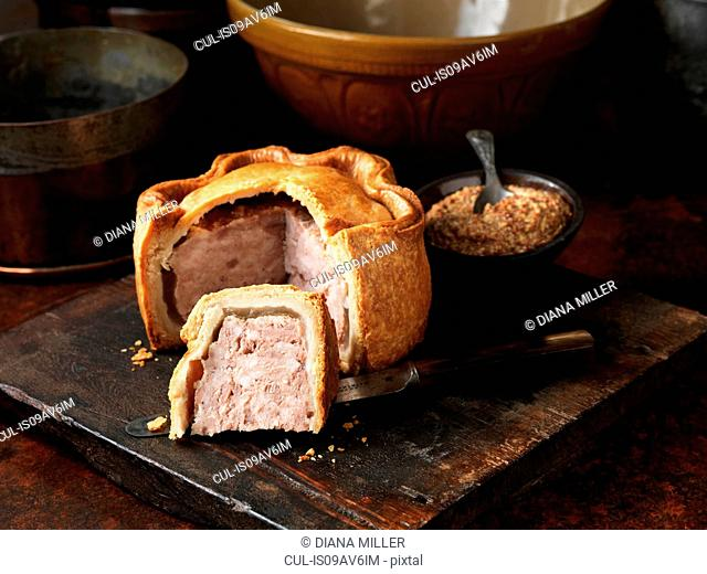 Sliced Melton Mowbray pork pie with wholegrain mustard on wooden cutting board