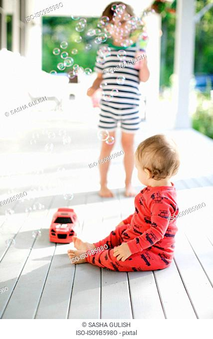 Male toddler sitting on porch watching boy blowing bubbles