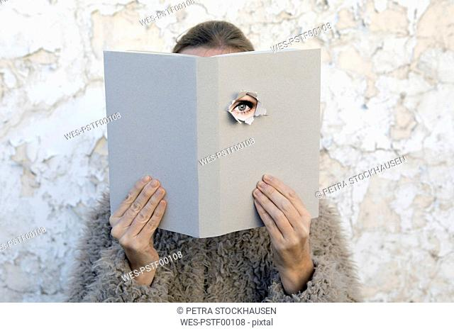 Woman covering face with book, reading poetry, eye looking through cover