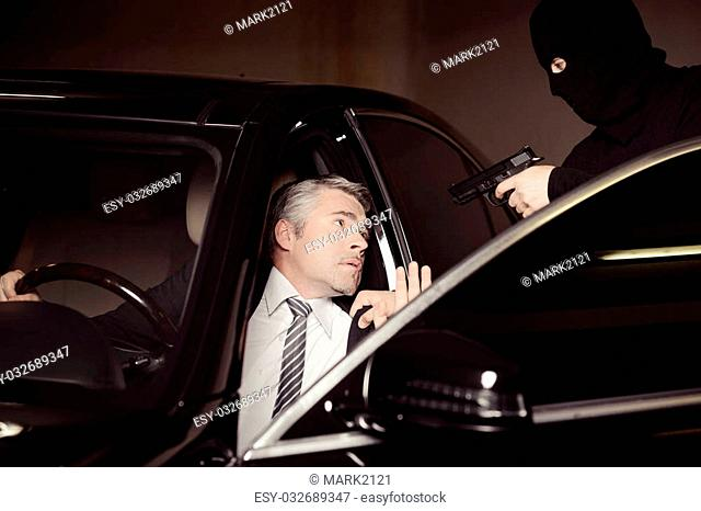 Attacking a businessman. Men in black balaclava holding gun and aiming a shocked mature businessman sitting on the front seat of a car