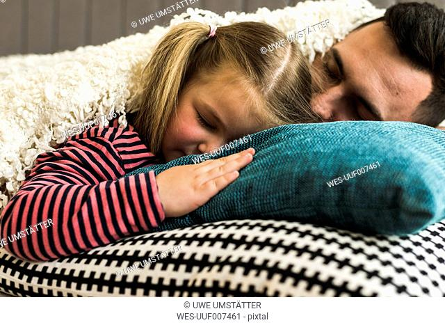 Father and daughter sleeping on cushion