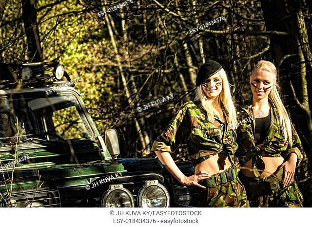 Beautiful girls on camouflage outfit, teamwork and off-road vehicle
