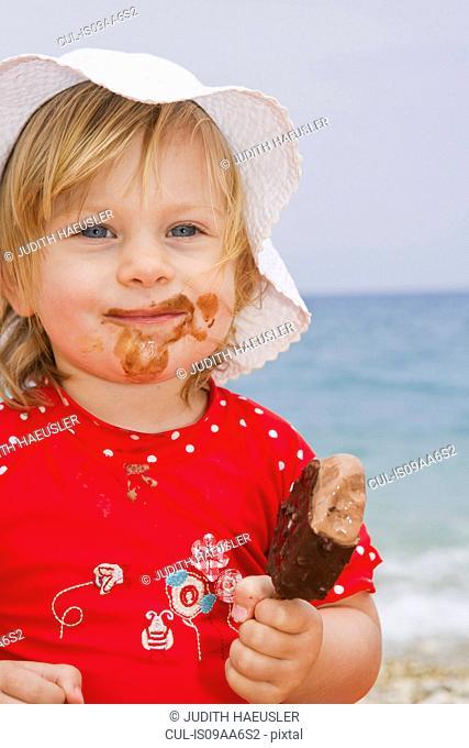 Baby girl eating ice cream on beach