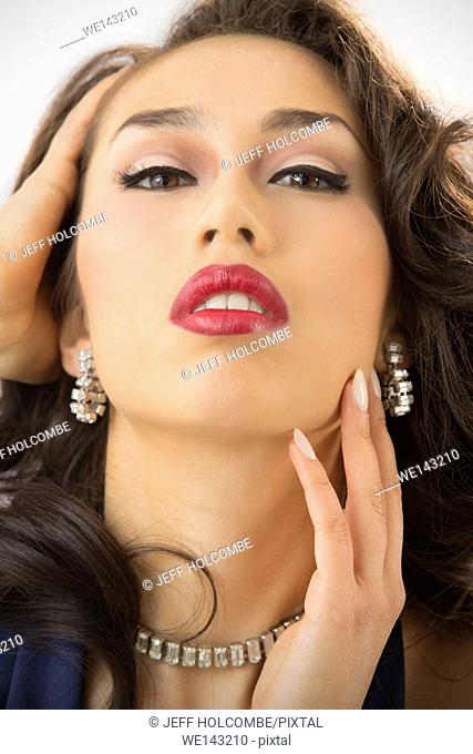 Beautiful young woman head and shoulders portrait, with head back and a glamorous look, hand in hair