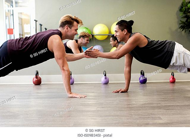 Friends in gym balancing on one hand, face to face smiling