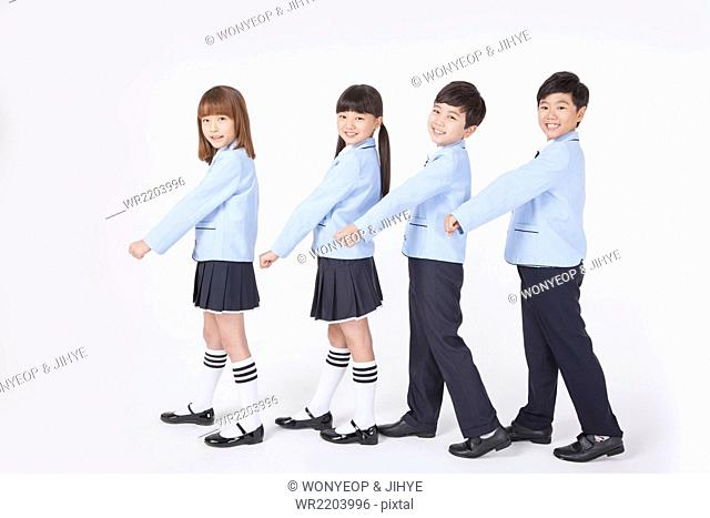 Four elementary school students in school uniforms standing in line and walking together with a smile