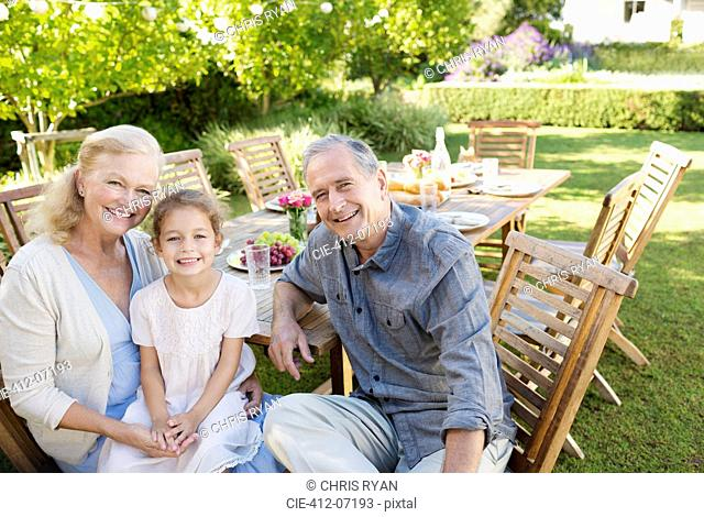 Older couple and granddaughter smiling outdoors