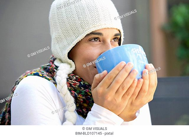 Hispanic woman drinking coffee outdoors